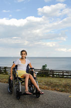 Girl in a wheelchair by the sea